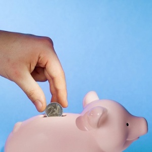 Close-up of human hand inserting two euro coin into piggy bank